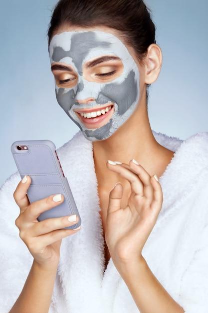 Lächelndes mädchen mit maske des lehms auf ihrem gesicht und liest eine mitteilung am telefon Premium Fotos