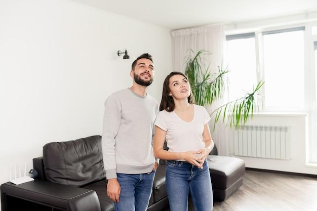 Lächelndes neugieriges junges paar in lässigen outfits, die im zimmer mit modernen möbeln stehen und wohnung zur miete sehen Premium Fotos