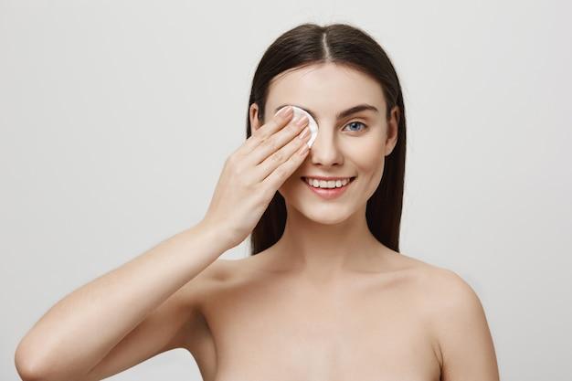 Lächelndes niedliches frauen-start-make-up mit wattepad Kostenlose Fotos