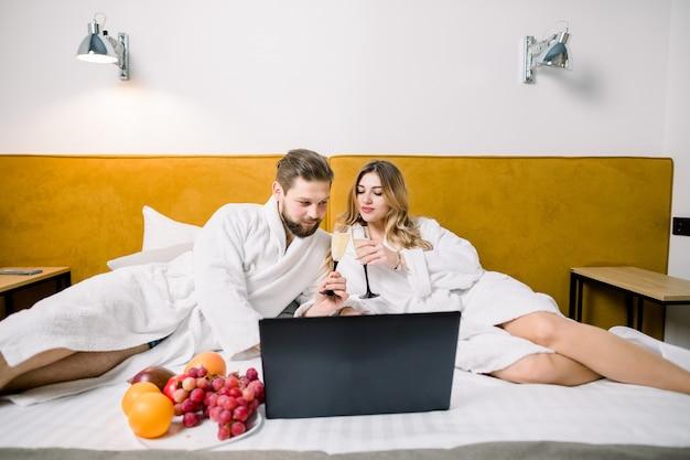 Lächelndes paar mit champagnergläsern im bett, mit laptop. paar, das alkohol trinkt, der auf dem bett im hotel sitzt Premium Fotos
