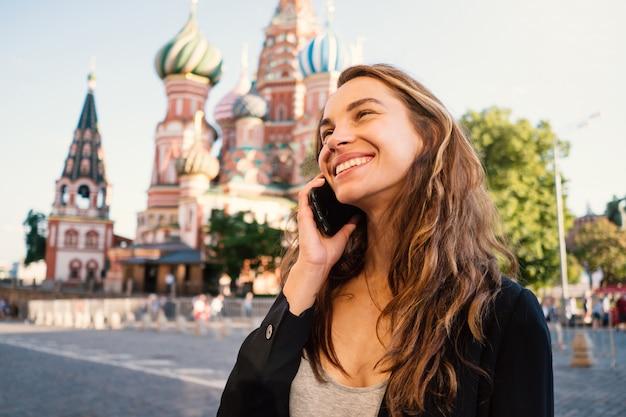 Lächelndes porträt der jungen frau auf dem roten platz sprechend am telefon, mit kathedrale des heiligen basilikums im hintergrund. moskau, russland. Premium Fotos