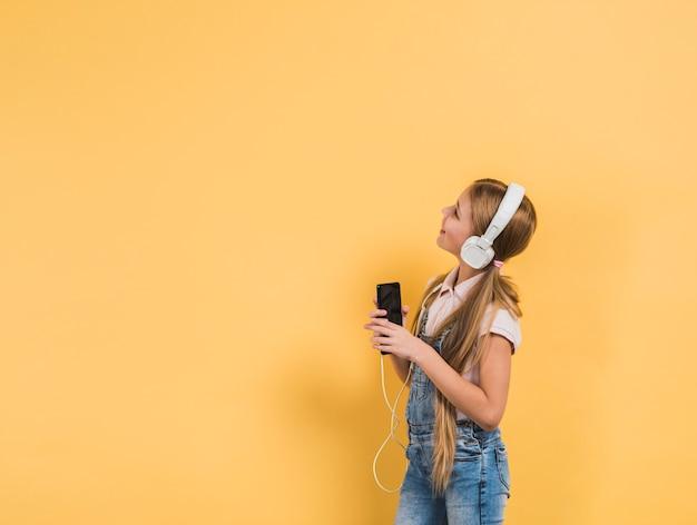 Lächelndes porträt einer hörenden musik des mädchens auf dem kopfhörer, der in der hand smartphone hält, gelben hintergrund betrachtend Kostenlose Fotos