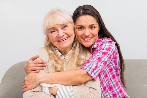 Lächelndes porträt einer jungen frau, die ihre ältere mutter umfasst Kostenlose Fotos