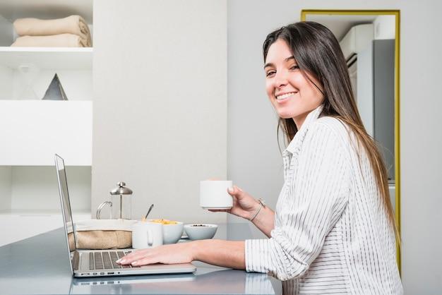 Lächelndes porträt einer jungen frau, die in der hand kaffeetasse unter verwendung des laptops hält Kostenlose Fotos