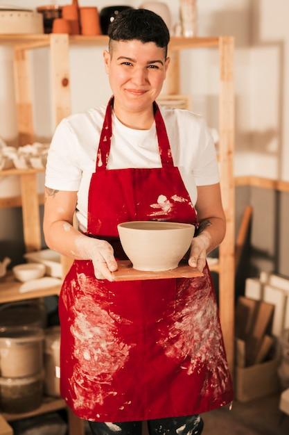 Lächelndes porträt einer jungen frau im roten schutzblech, das handgemachte lehmschüssel auf hölzernem behälter hält Kostenlose Fotos