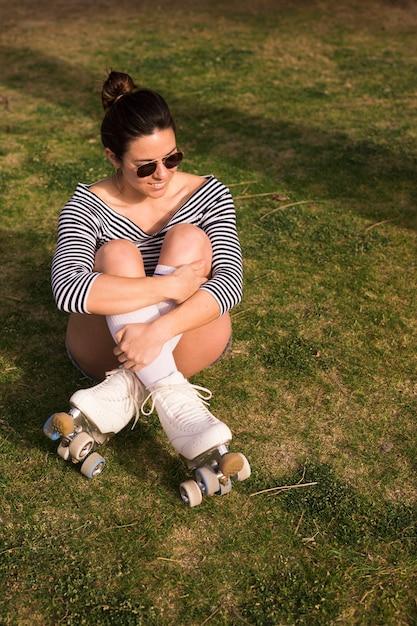 Lächelndes porträt einer jungen frau mit ihren gekreuzten beinen, die auf grünem gras sitzen Kostenlose Fotos