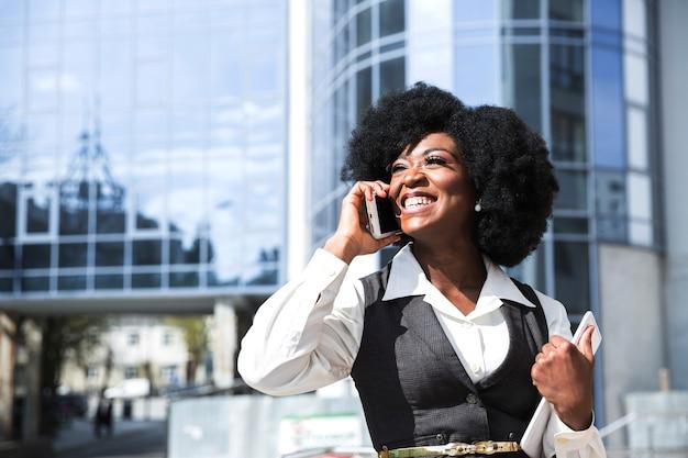 Lächelndes porträt einer überzeugten jungen geschäftsfrau, welche die digitale tablette spricht am handy hält Kostenlose Fotos