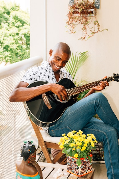 Lächelndes porträt eines afrikanischen jungen mannes, der auf dem stuhl spielt die gitarre im balkon sitzt Kostenlose Fotos