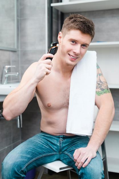 Lächelndes porträt eines hemdlosen jungen mannes, der im badezimmer rasiert mit elektrorasierer sitzt Kostenlose Fotos
