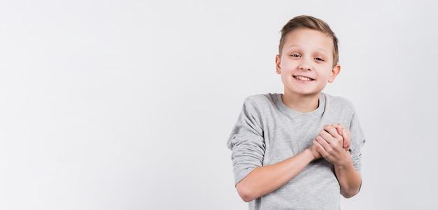 Lächelndes porträt eines jungen, der die hände schaut zur kamera gegen weißen hintergrund verbindet Kostenlose Fotos