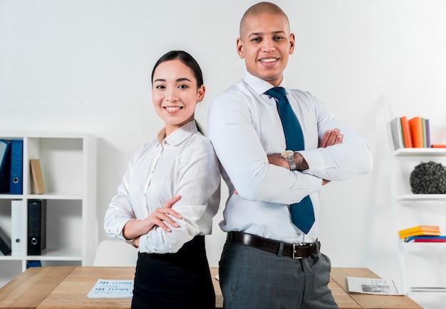 Lächelndes porträt eines jungen geschäftsmannes und der geschäftsfrau, die zurück zu rückseite im büro stehen Kostenlose Fotos