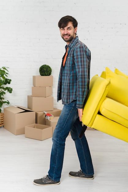 Lächelndes porträt eines jungen mannes, der das gelbe sofa im neuen haus anhebt Kostenlose Fotos