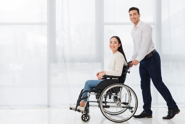 Lächelndes porträt eines jungen mannes, der die behinderte frau sitzt auf dem rollstuhl betrachtet kamera drückt Kostenlose Fotos