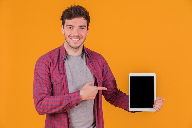 Lächelndes porträt eines jungen mannes, der etwas auf digitaler tablette gegen einen orange hintergrund zeigt Kostenlose Fotos