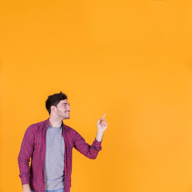 Lächelndes porträt eines jungen mannes, der etwas auf einem orange hintergrund zeigt Kostenlose Fotos