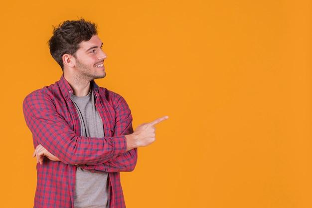 Lächelndes porträt eines jungen mannes, der seinen finger gegen einen orange hintergrund zeigt Kostenlose Fotos