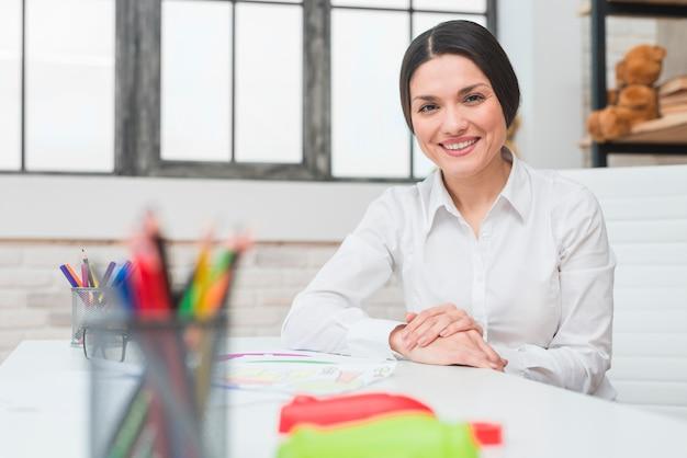 Lächelndes porträt eines jungen überzeugten weiblichen psychologen, der in ihrem büro sitzt Kostenlose Fotos