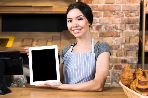 Lächelndes porträt eines jungen weiblichen bäckers, der die digitale tablette steht am bäckereizähler hält Kostenlose Fotos