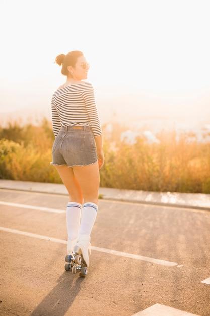 Lächelndes porträt eines jungen weiblichen schlittschuhläufers, der auf straße steht Kostenlose Fotos