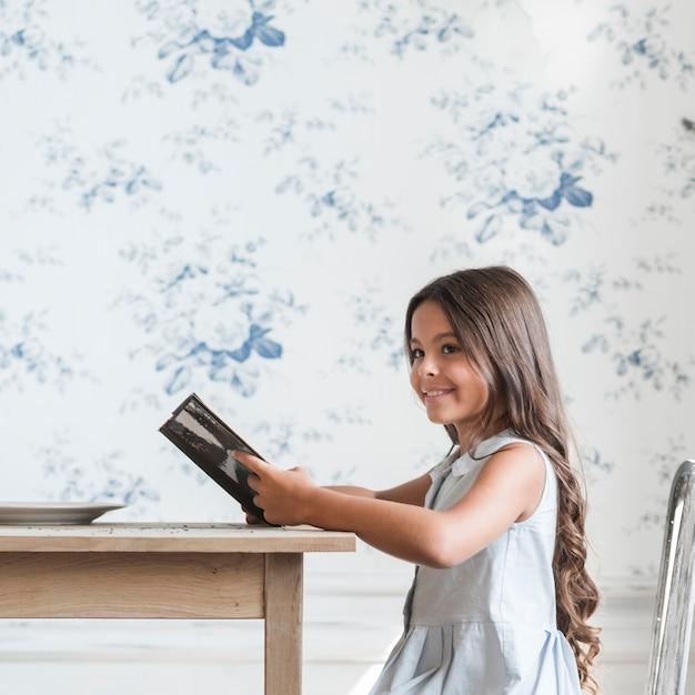 Lächelndes porträt eines mädchenlesens, das vor tapetenlesebuch sitzt Kostenlose Fotos