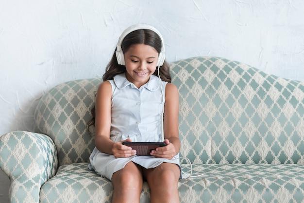 Lächelndes porträt eines mädchens, das auf sofa unter verwendung des handys mit kopfhörer auf ihrem kopf sitzt Kostenlose Fotos