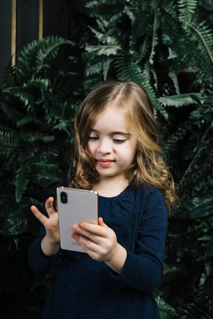 Lächelndes porträt eines mädchens, das gegen anlagen unter verwendung des handys steht Kostenlose Fotos