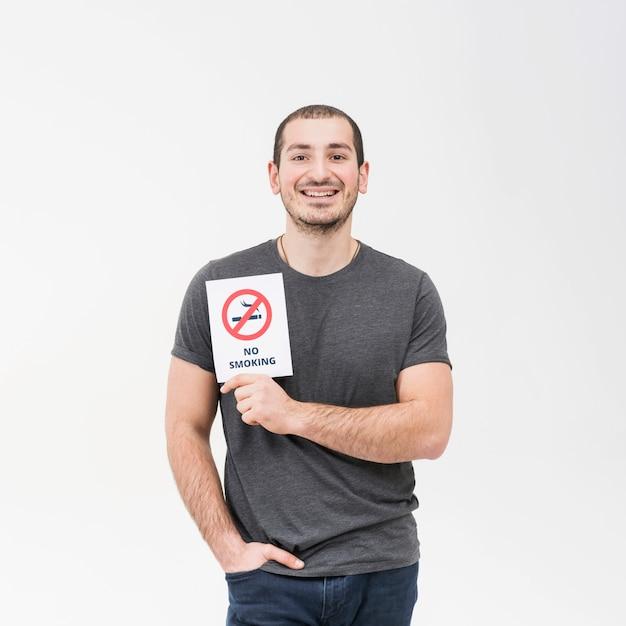 Lächelndes porträt eines mannes, der nichtraucherzeichen mit der hand in seiner tasche lokalisiert auf weißem hintergrund zeigt Kostenlose Fotos