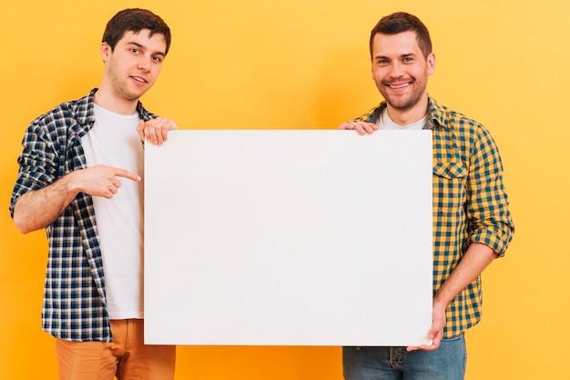 Lächelndes porträt eines mannes, der weißes leeres plakat gegen gelben hintergrund zeigt Kostenlose Fotos