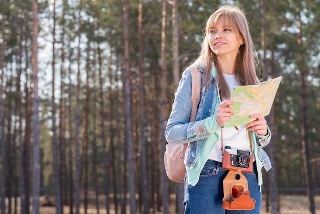 Lächelndes porträt eines weiblichen wanderers, der in der hand die karte wandert im wald hält Kostenlose Fotos