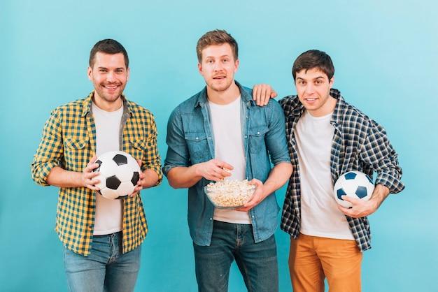 Lächelndes porträt von den freunden, die fußballspiel gegen blauen hintergrund aufpassen Kostenlose Fotos