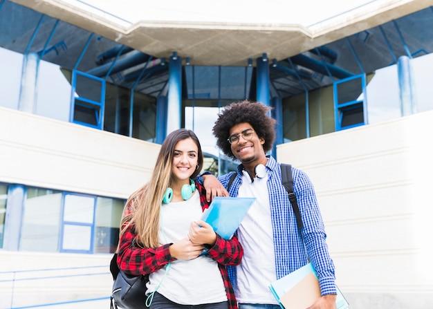 Lächelndes porträt von den jungen paaren, die in der hand die bücher stehen vor dem hochschulgebäude schauend zur kamera halten Kostenlose Fotos