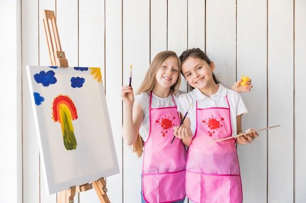 Lächelndes porträt von den mädchen, die den malerpinsel und -palette stehen nahe dem gestell mit gezogenem malen halten Kostenlose Fotos