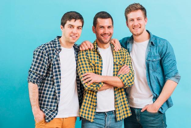 Lächelndes porträt von drei männlichen freunden, die gegen blauen hintergrund stehen Kostenlose Fotos