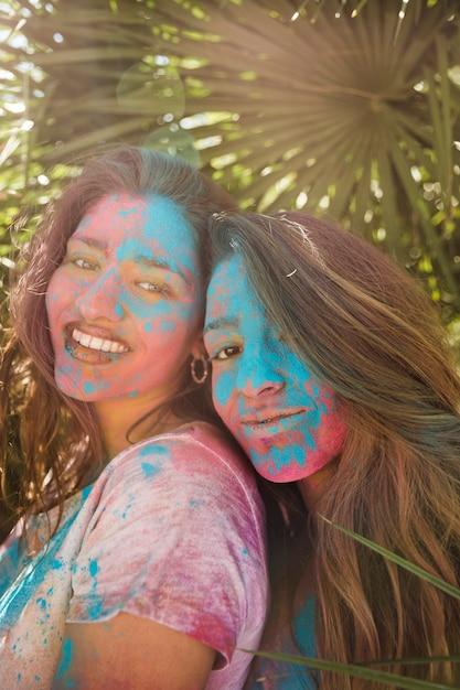 Lächelndes porträt von junge frauen mit holi farbe auf ihrem gesicht, das kamera betrachtet Kostenlose Fotos