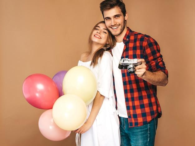Lächelndes schönes mädchen und ihr hübscher freund, die bündel bunte ballone hält. glückliches paar, das foto von selbst auf retro- kamera macht. alles gute zum geburtstag Kostenlose Fotos