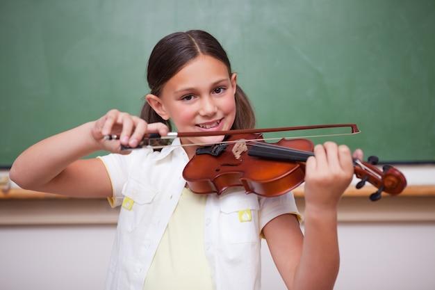 Lächelndes schulmädchen, welches die violine spielt Premium Fotos