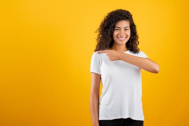 Lächelndes schwarzes mädchen, das finger auf das copyspace getrennt über gelb zeigt Premium Fotos