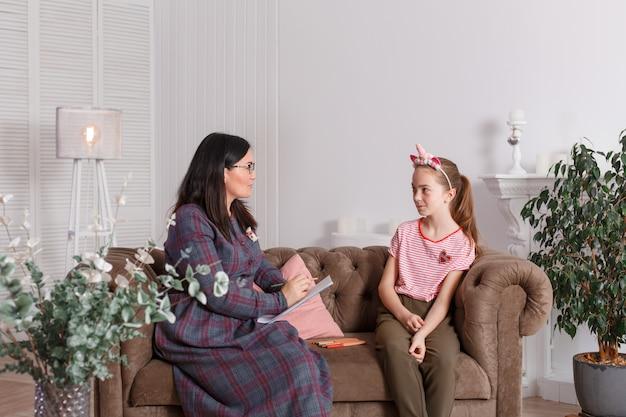 Lächelndes sitzen des mädchens auf einem sofa nahe bei einem sitzenden ärztintherapeuten Premium Fotos