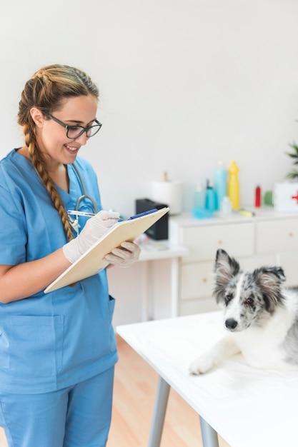 Lächelndes weibliches tierarztschreiben auf klemmbrett mit hund auf tabelle in der klinik Kostenlose Fotos