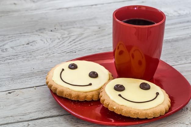 Lächelnplätzchen auf einem roten teller mit tasse kaffee, hölzernem hintergrund, essen Kostenlose Fotos