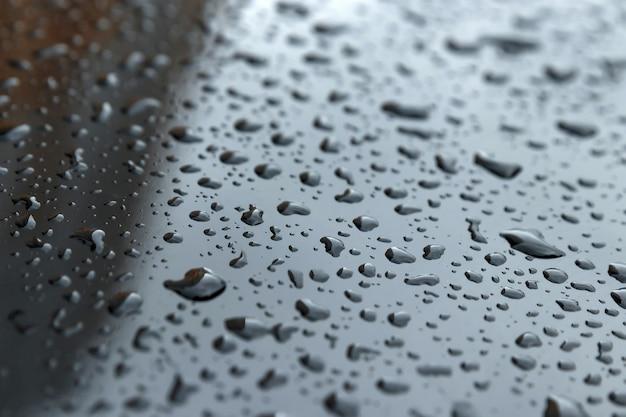 Lässt nahaufnahme auf einer dunklen haube fallen. konzept von regen, kondensation Premium Fotos