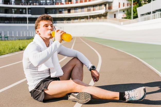 Läufer, der ein energiegetränk trinkt Kostenlose Fotos