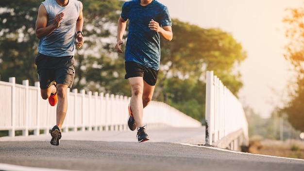 Läufer der jungen leute, der auf laufender straße im stadtpark läuft Premium Fotos