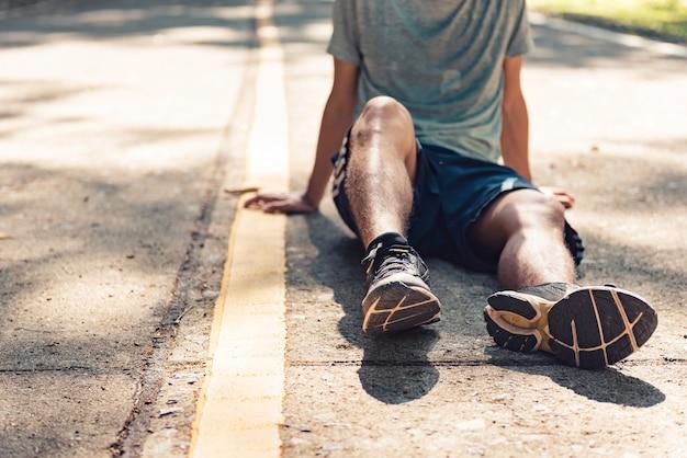 Läufer des jungen mannes, der nach training am sonnigen morgen stillsteht. Premium Fotos