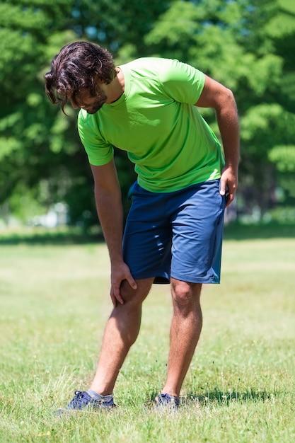Läufer mit beinschmerzen im park Premium Fotos