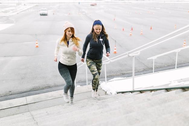 Läufer mit zwei frauen, der auf dem treppenhaus im winter rüttelt Kostenlose Fotos