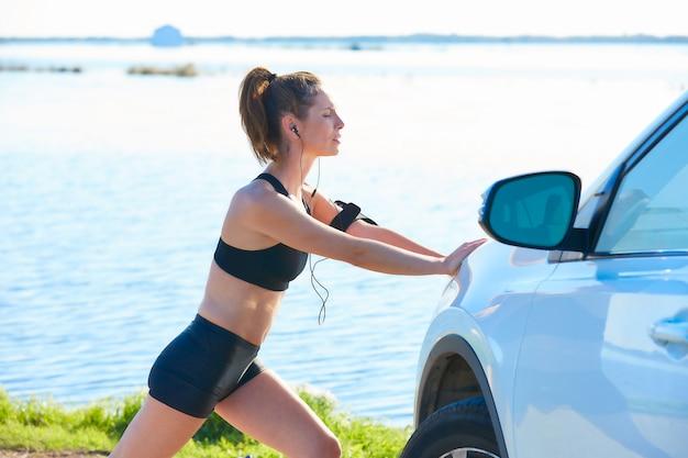 Läuferfrau, die auf ein auto im see ausdehnt Premium Fotos