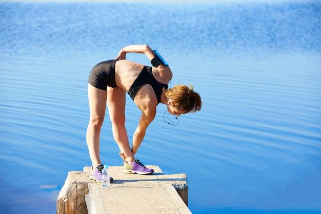 Läuferfrau, die in einen see im freien ausdehnt Premium Fotos