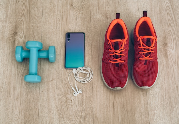 Läuferturnschuhe mit smartphone, kopfhörern und hanteln Premium Fotos