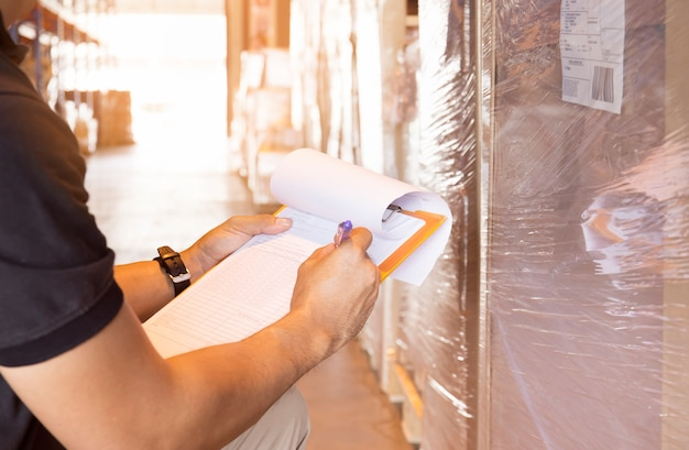 Lagerarbeiter halten ein klemmbrett, das auf datenblatt mit inventar der produkte schreibt. Premium Fotos
